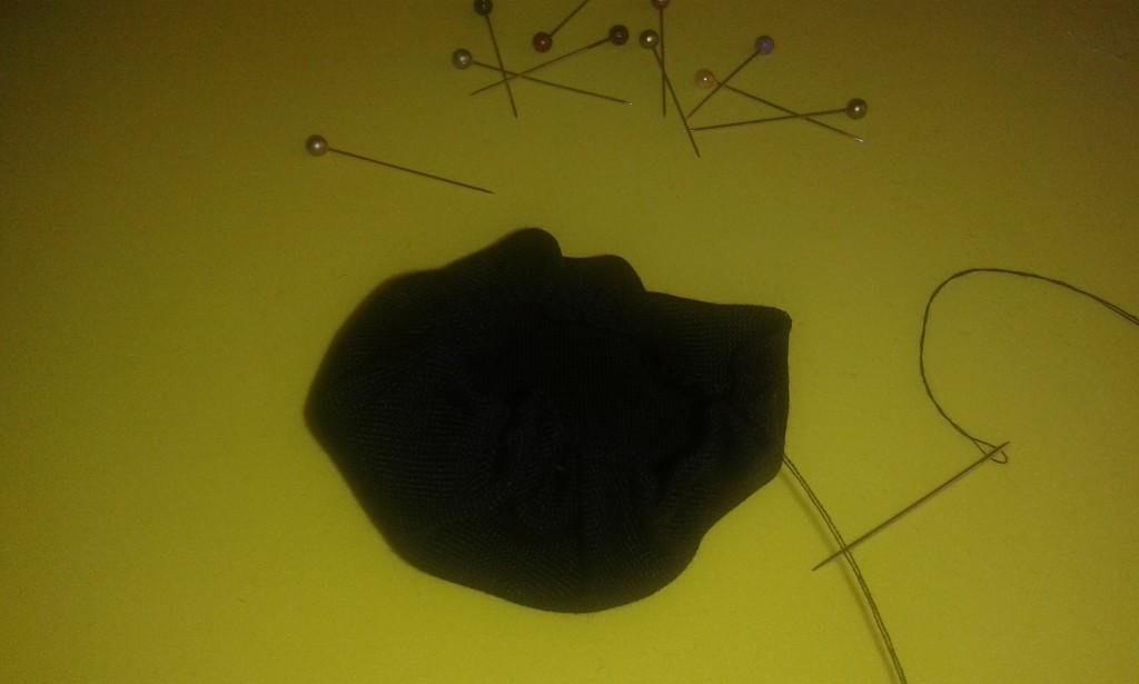 El círculo de tela con el hilo y la aguja siguiendo el margen