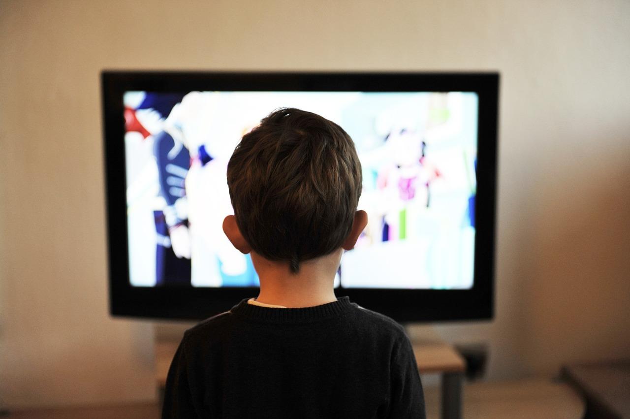 Un niño abstraído viendo la televisión