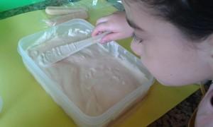 Esparciendo la crema sobre los bizcochos