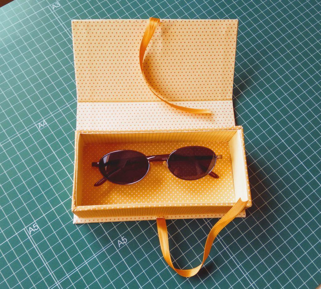 Caja libro abierta con las gafas en su interior