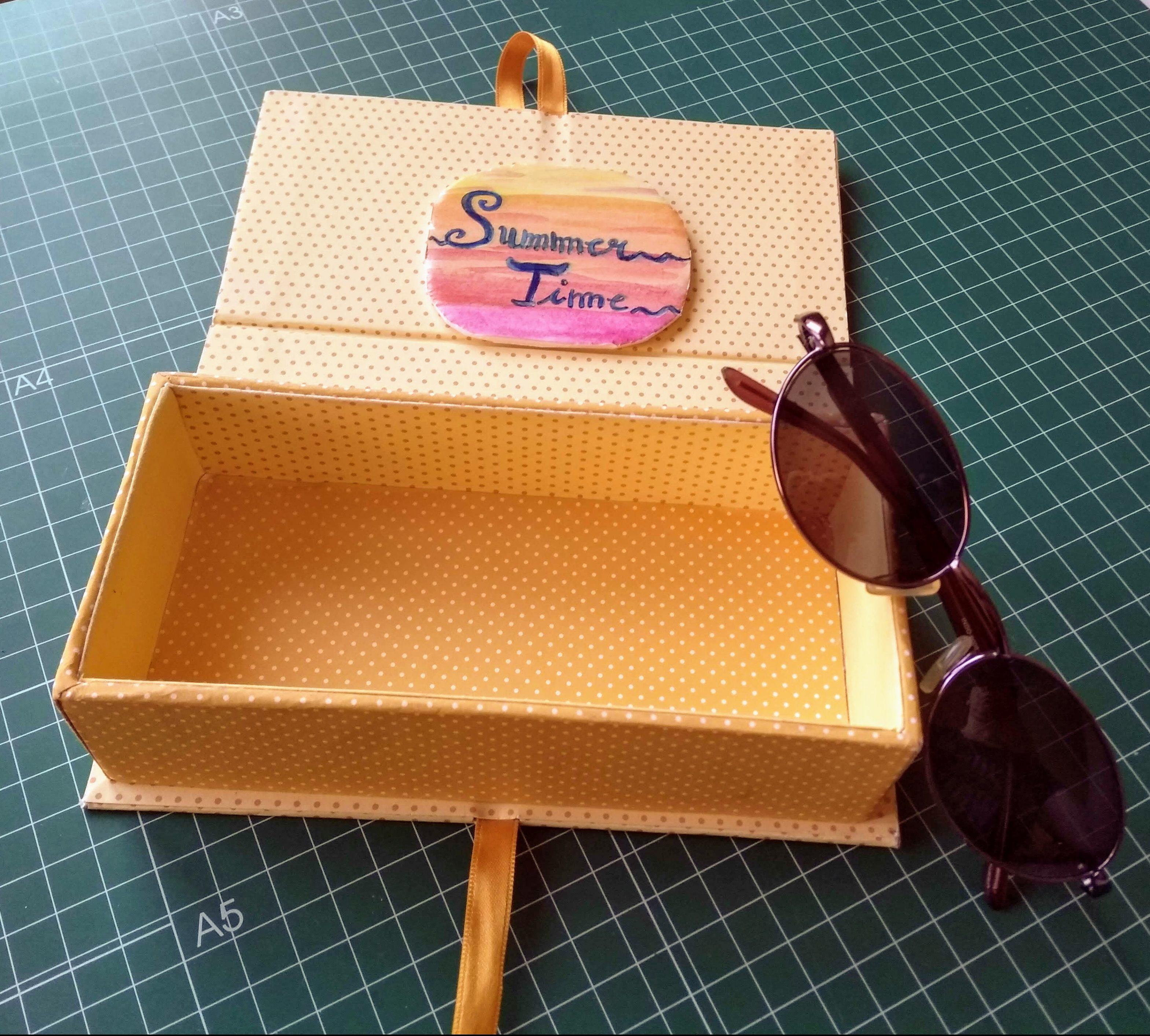 Caja libro abierta con las gafas al lado
