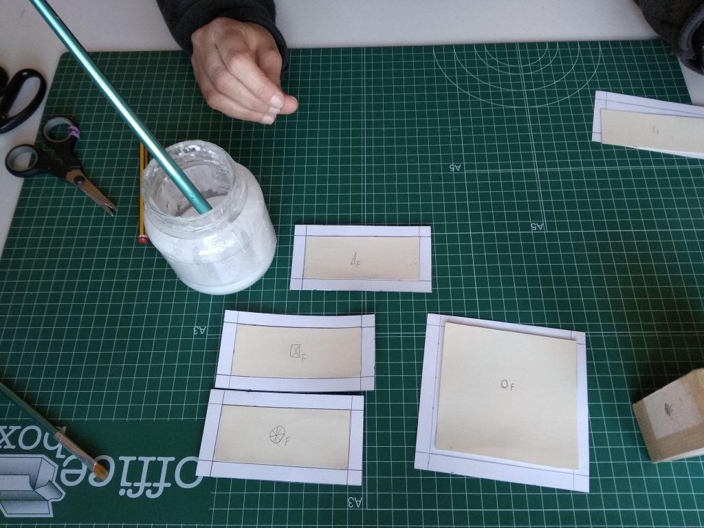 Piezas con la estracilla pegada al papel decorado donde se aprecia la prolongación de las líneas que delimitan la estracilla