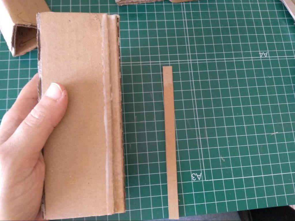 Añadiendo una tira de cartón para rectificar una pata