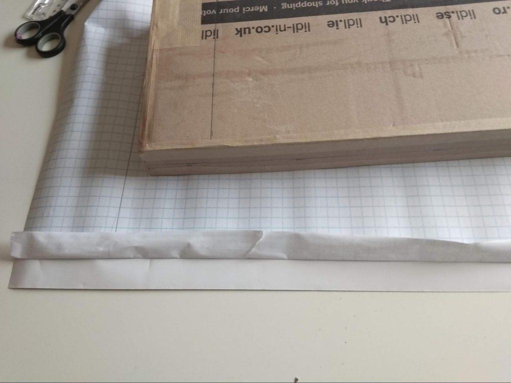 El estante sobre la cuadrícula del papel adhesivo a punto para ser forrado