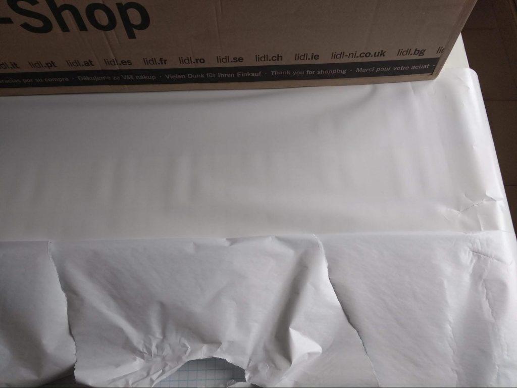 Pegado del papel adhesivo a un lateral del estante de cartón
