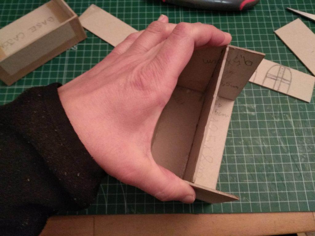 Sujetando las piezas con la mano para que el suelo de la casa se adhiera bien