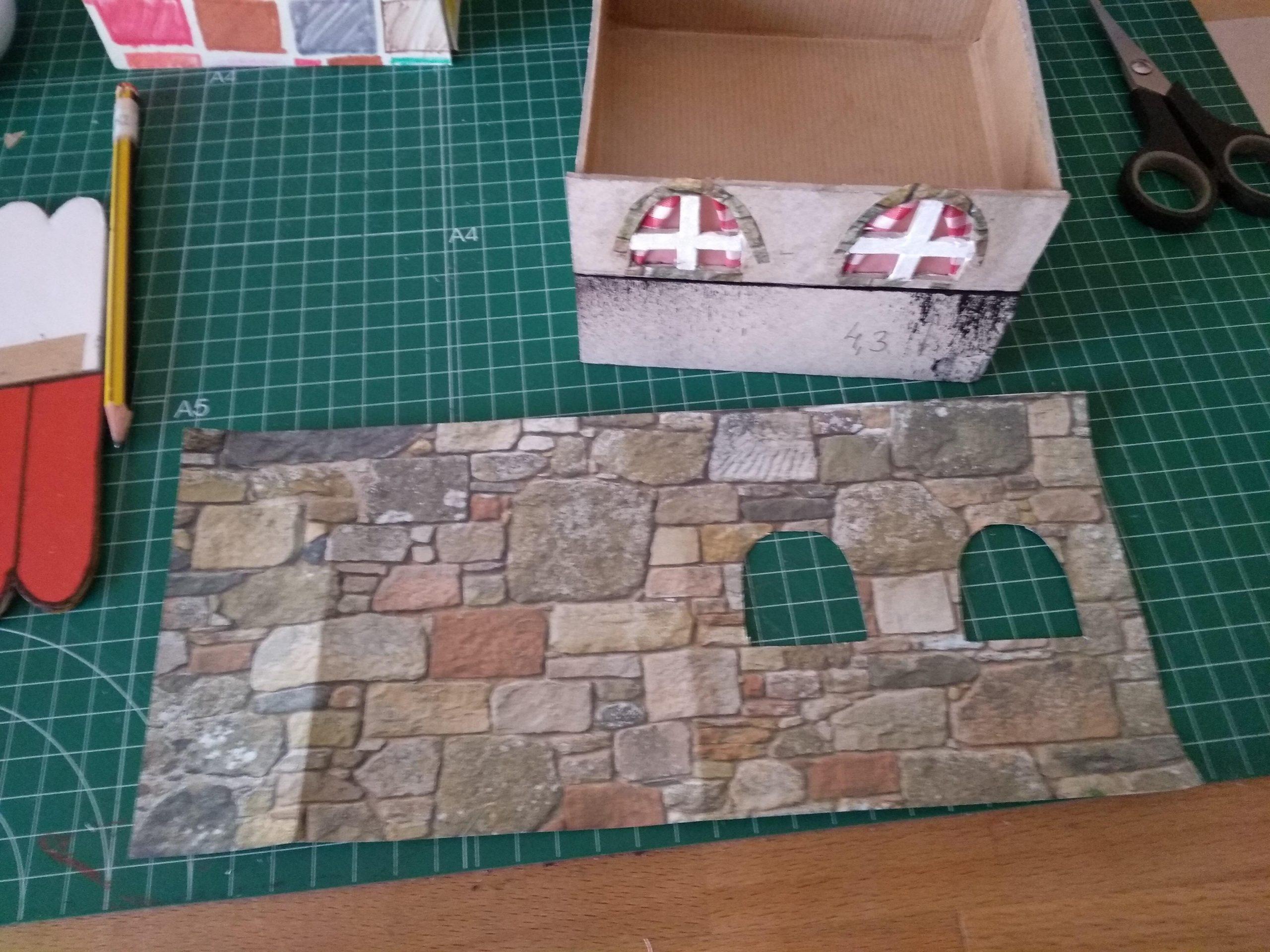 Casita de Navidad a punto de pegarle el papel decorado simulando las piedras de las paredes