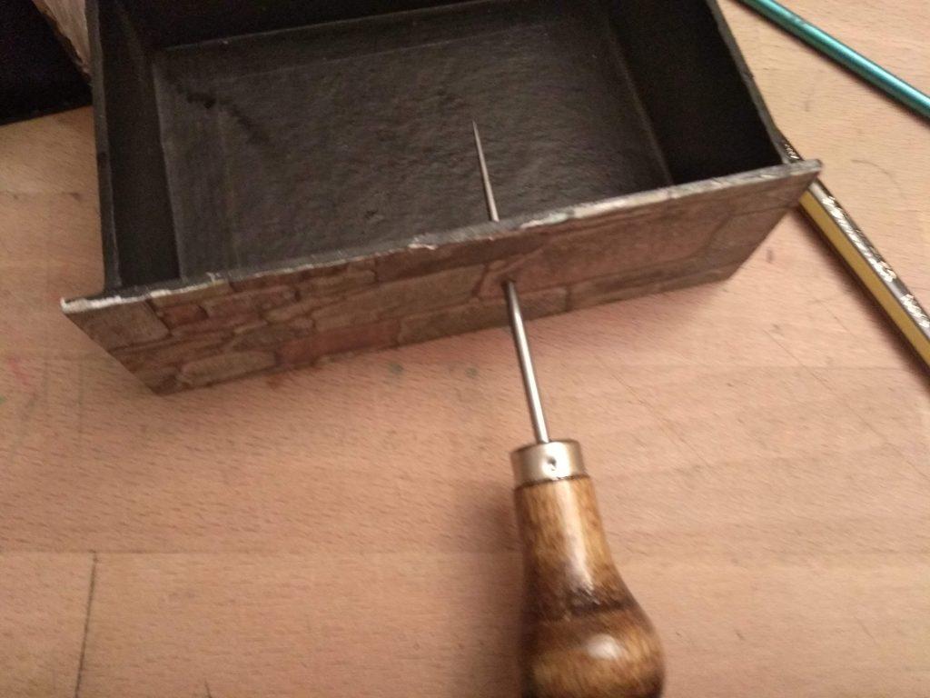 Agujereando el frontal del cajón con un punzón para ponerle el encuadernador de cabeza redonda