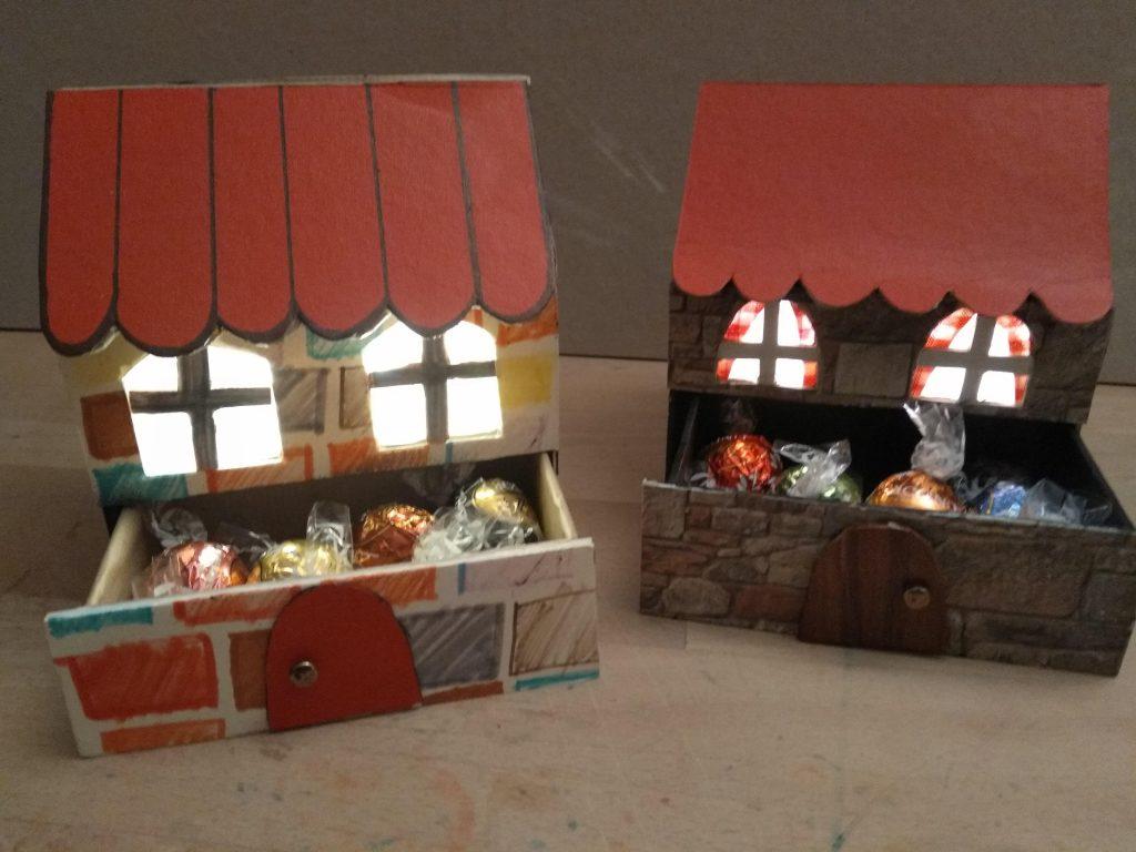 Imagen de dos casitas de cartón navideñas ya terminadas, con las luces led encendidas, y con los cajones abiertos y llenos de bombones