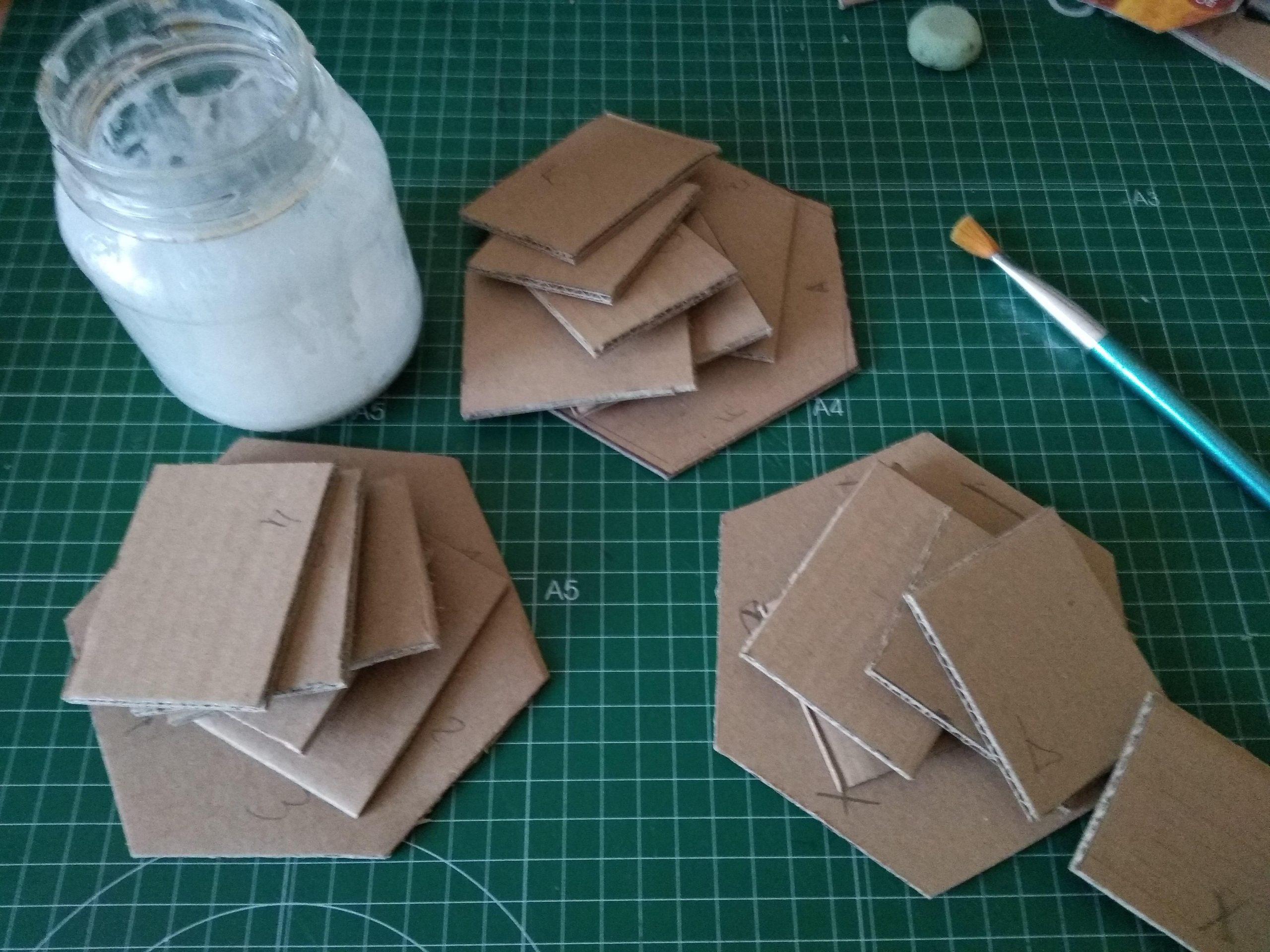 Piezas cortadas para hacer tres estantes en forma de colmena pequeños