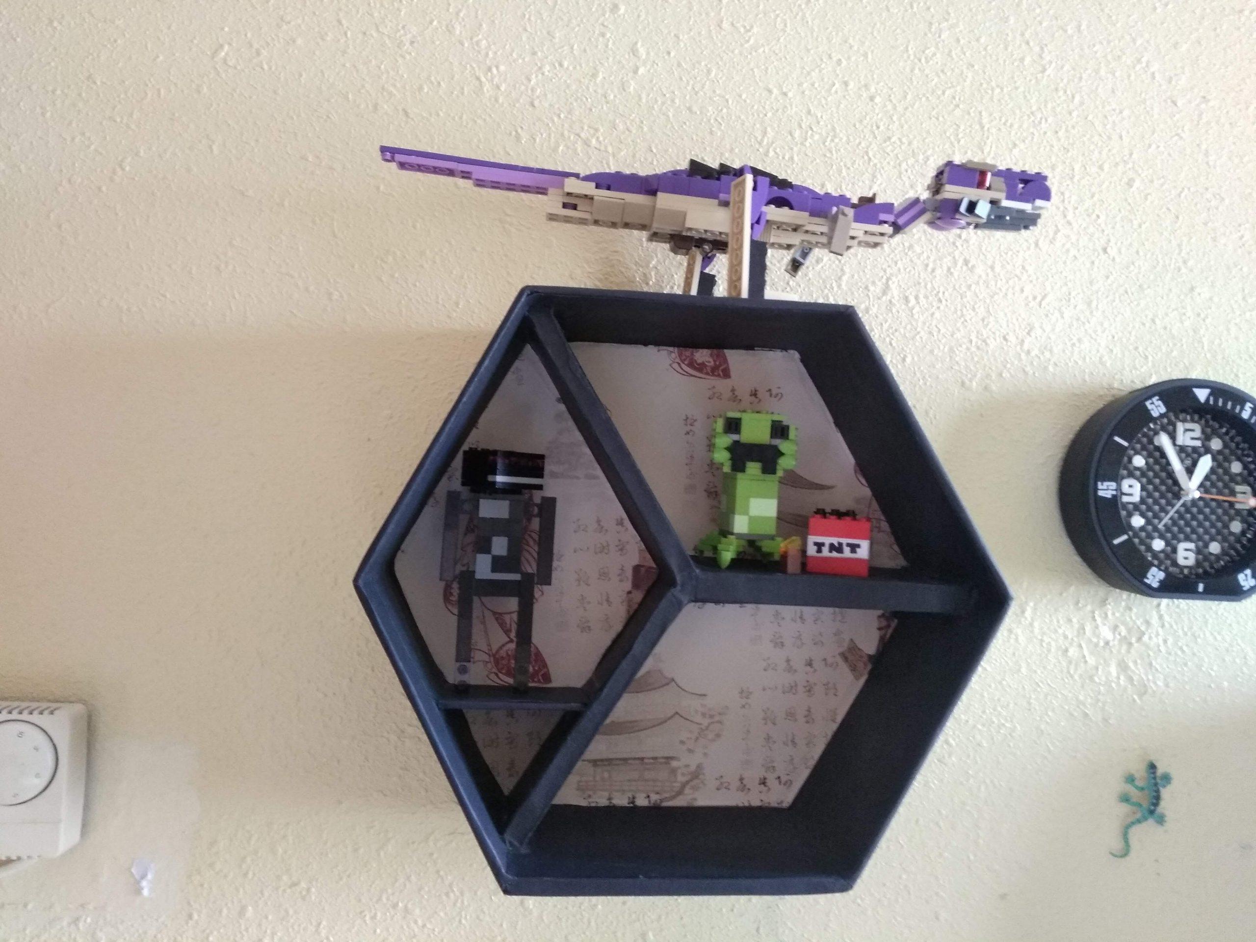 Estante grande con divisiones colgado en la pared y decorado con figuras de Lego